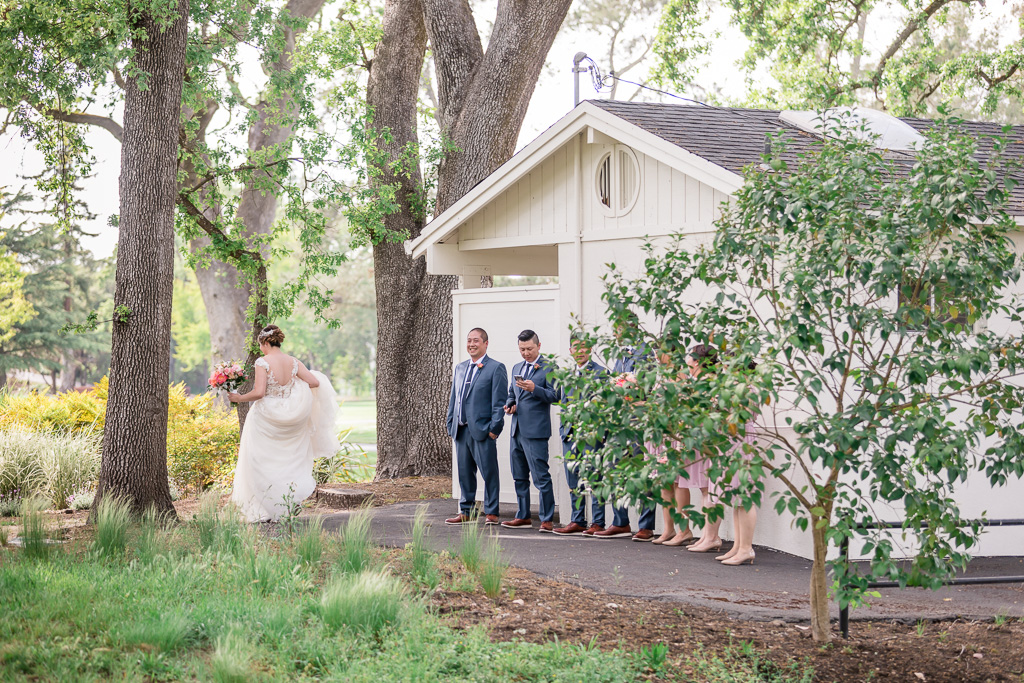 bride walking past wedding party for the first look