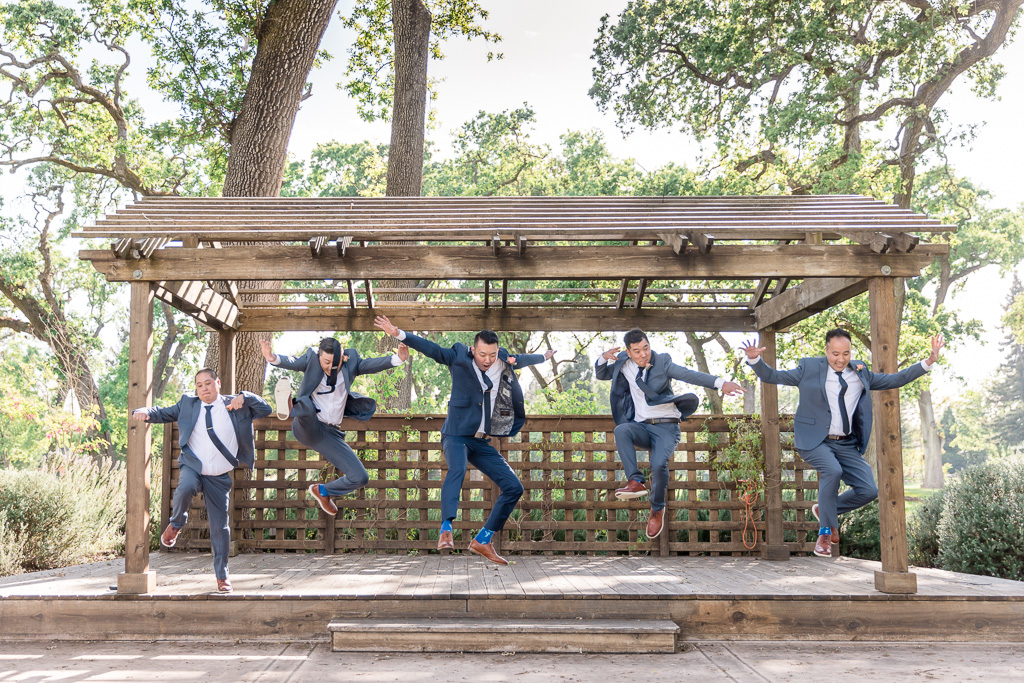 action shot of groom and groomsmen jumping off a step