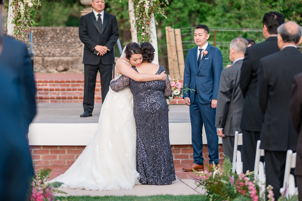 mom and bride hugging at the end of the aisle before wedding ceremony