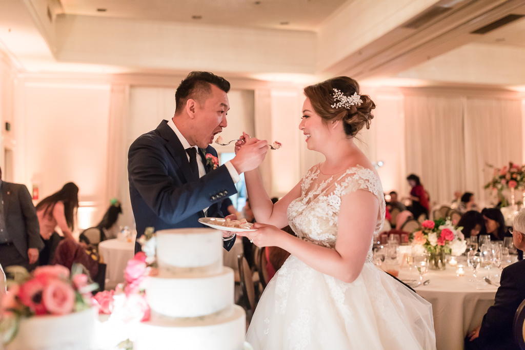 bride and groom peacefully feeding each other slices of cake