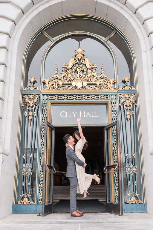 just-married bride and groom exiting San Francisco City Hall and happily excitedly cheering