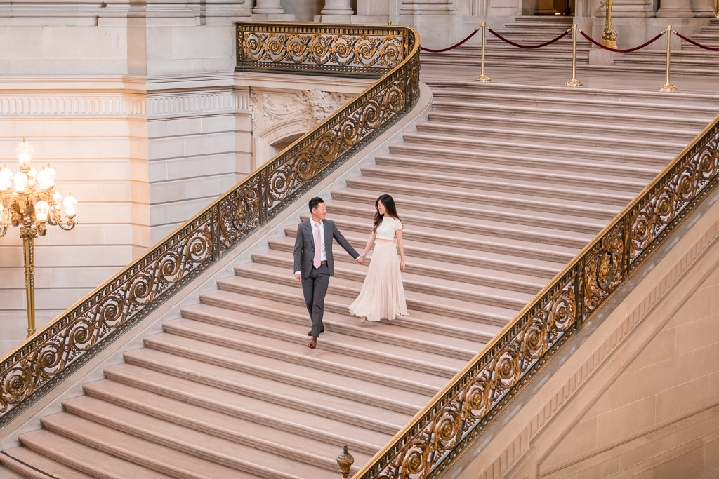 wedding portrait of bride and groom walking on grand staircase