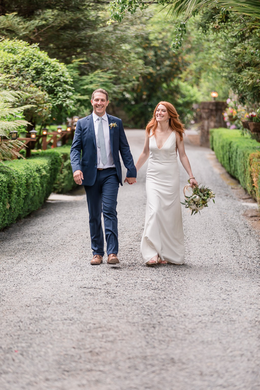 newlyweds walking towards their reception