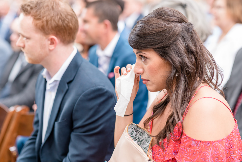 wedding guest wiping her tears during the ceremony