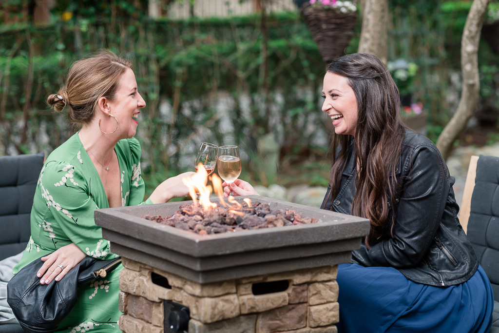 two wedding guests sitting by the deer park villa fire-pit to enjoy their cocktails