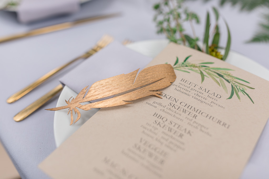 deer park villa wedding reception table setting with a piece of gold feather
