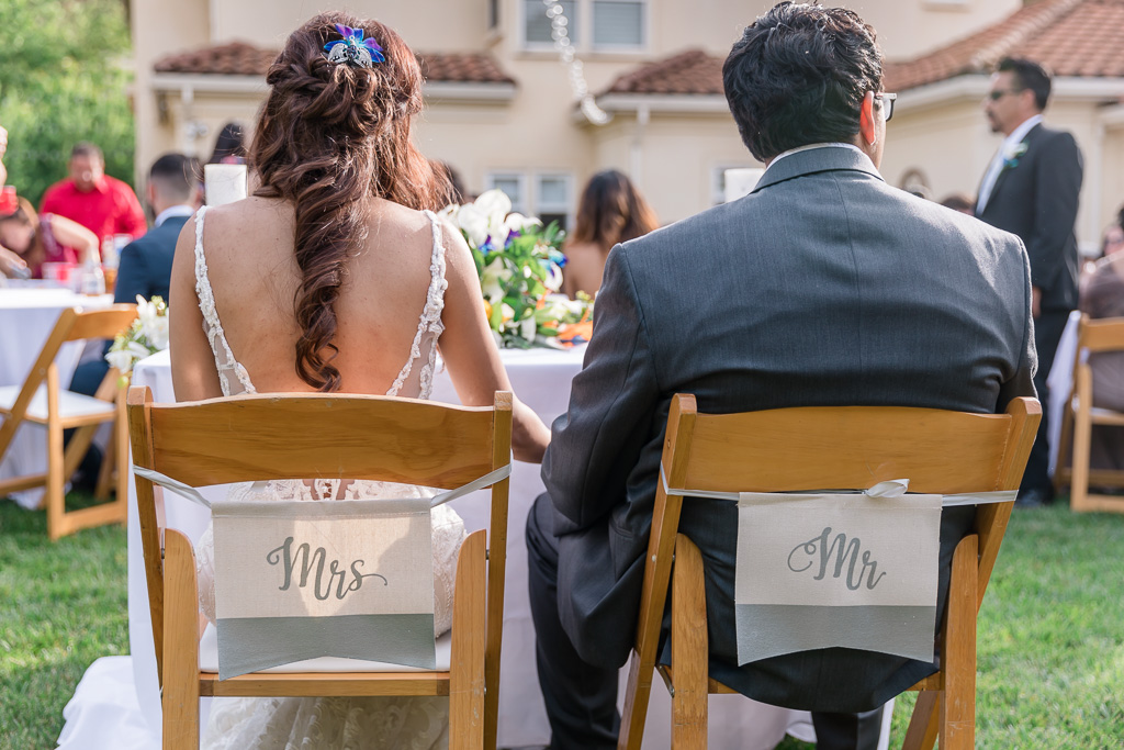 mr and mrs sign hanging on the chairs at the sweatheart table