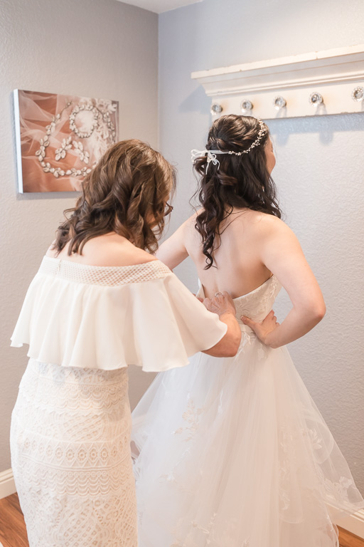 mom helping the bride with her dress
