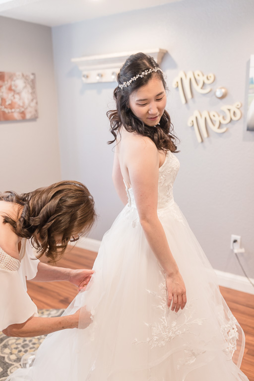 bride getting into her dress in the bridal room