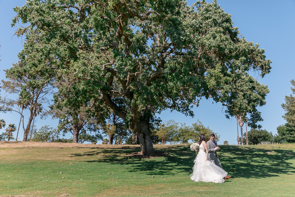 wedding first look next to a big oak tree on a golf course