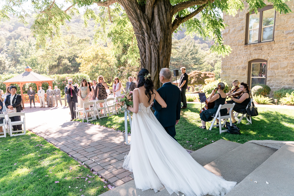 bride walks down the aisle with her father at Elliston Winery