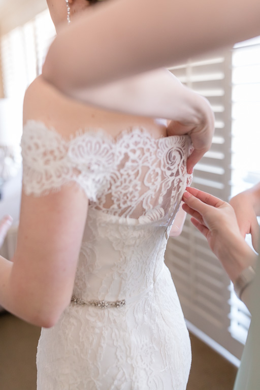 Bouttoning up the lace wedding dress