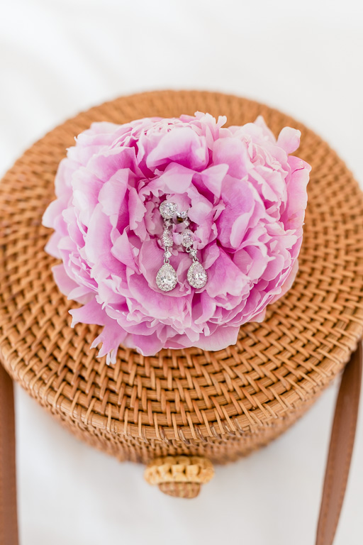 diamond earrings on top of a blush peony