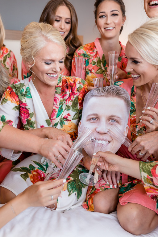 funny photo of the girls feeding the cardboard groom some champagne
