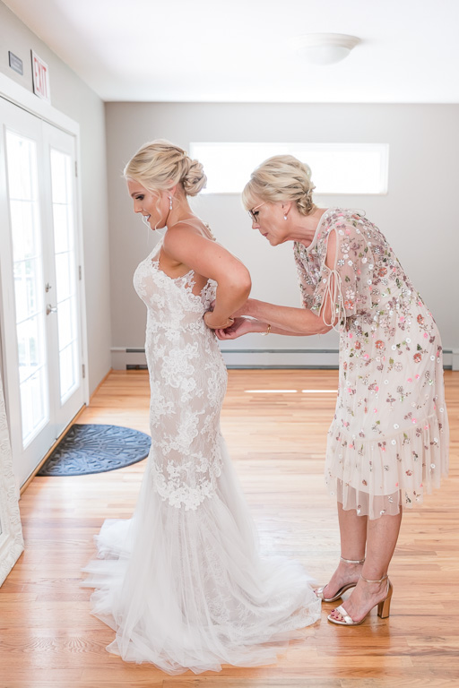 bride in her dress with the help of her mom