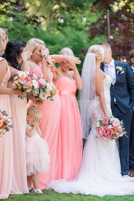funny and cute Seattle wedding photo of the flower girl covering her eyes for the newlyweds' kissing