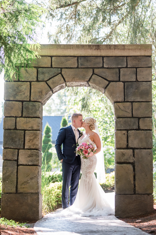 couple portrait under the stone arch at the Rock Creek Gardens