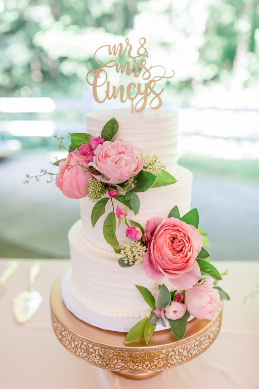 a plain wedding cake decorated with fresh flowers