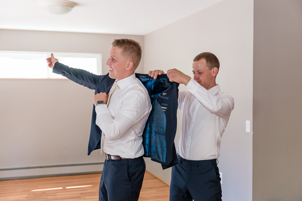 groom putting on his jacket with the help of his brother
