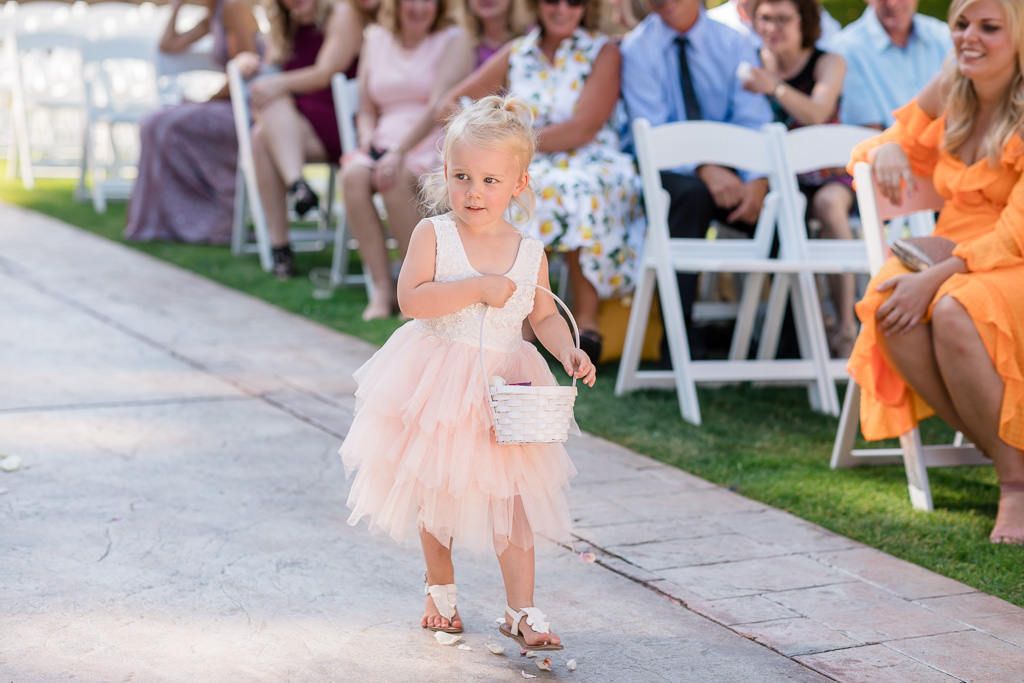 cute junior flower girl throwing petals