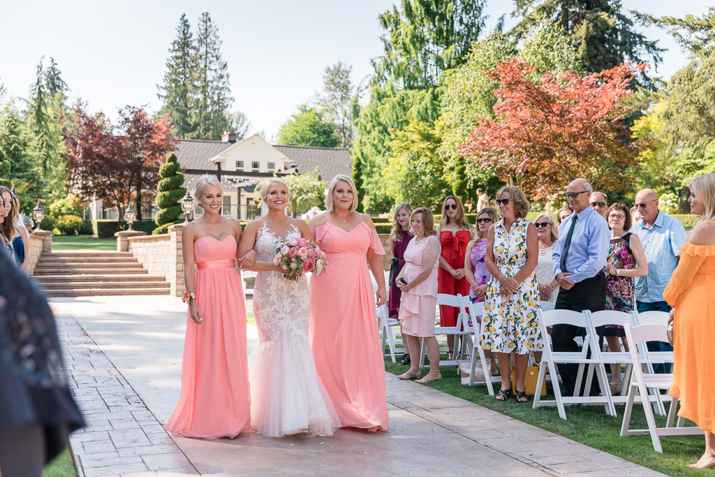 bride walks down the aisle escorted by her sisters