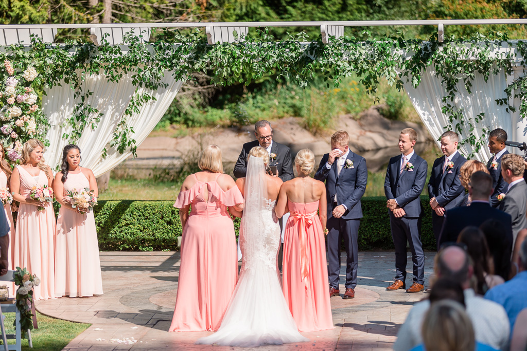 groom gets emotional when he sees his bride walking down the aisle at Rock Creek Gardens
