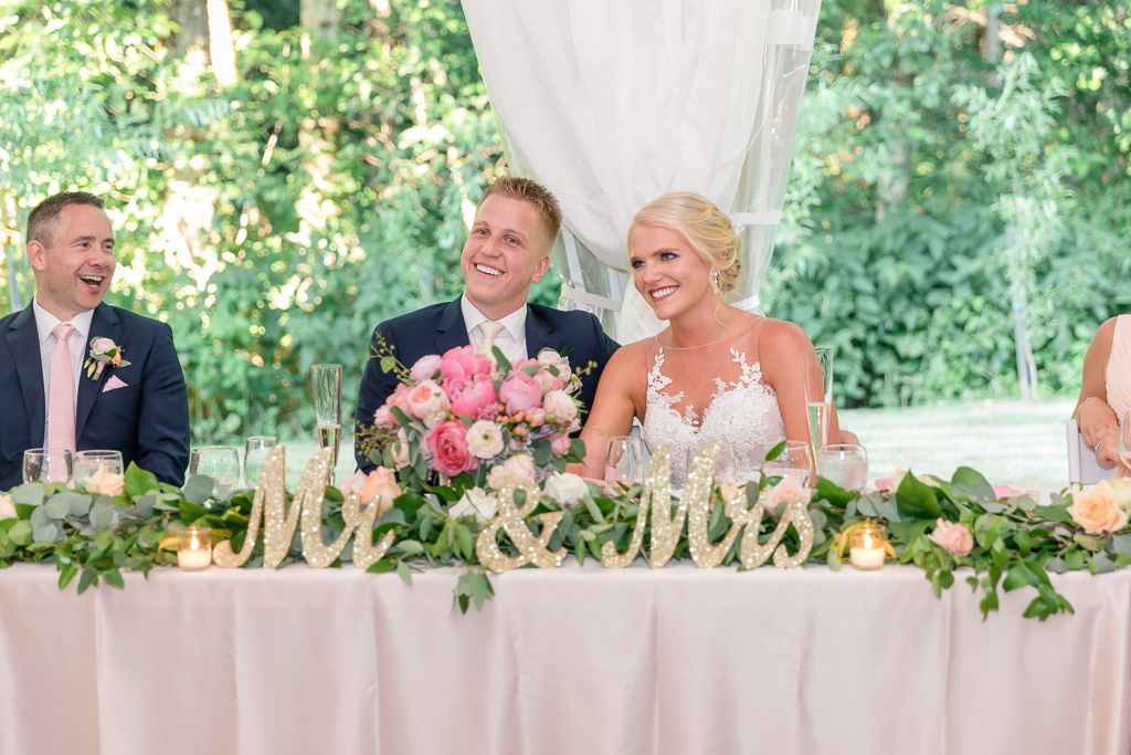 bride and groom at their head table under the tent