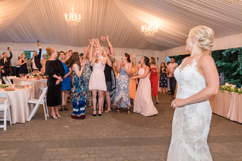 girls jumping up the air to catch the bouquet