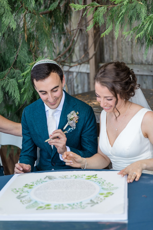 couples signing their beautifully designed ketubah