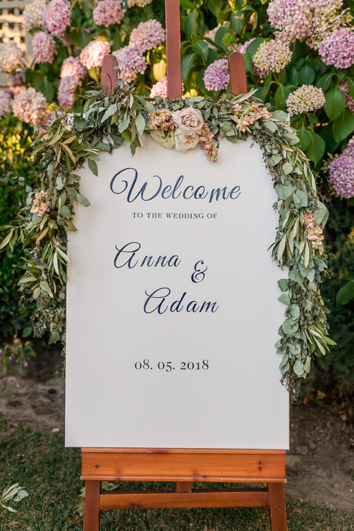 pretty wedding welcome sign in front of the flower wall