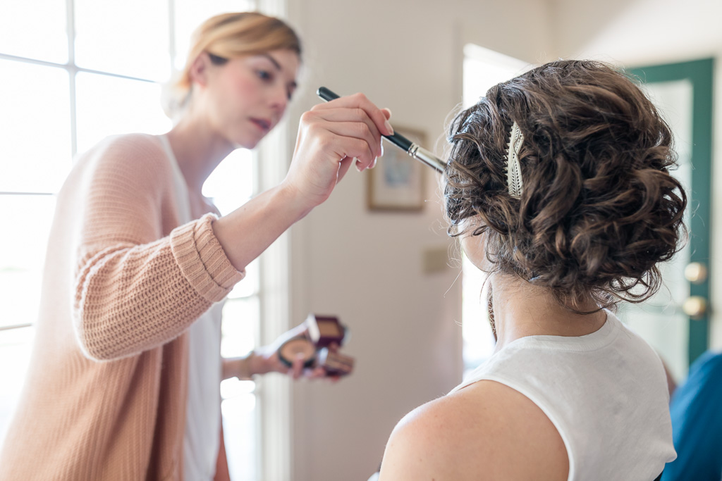 bride having her makeup and hair done in the house