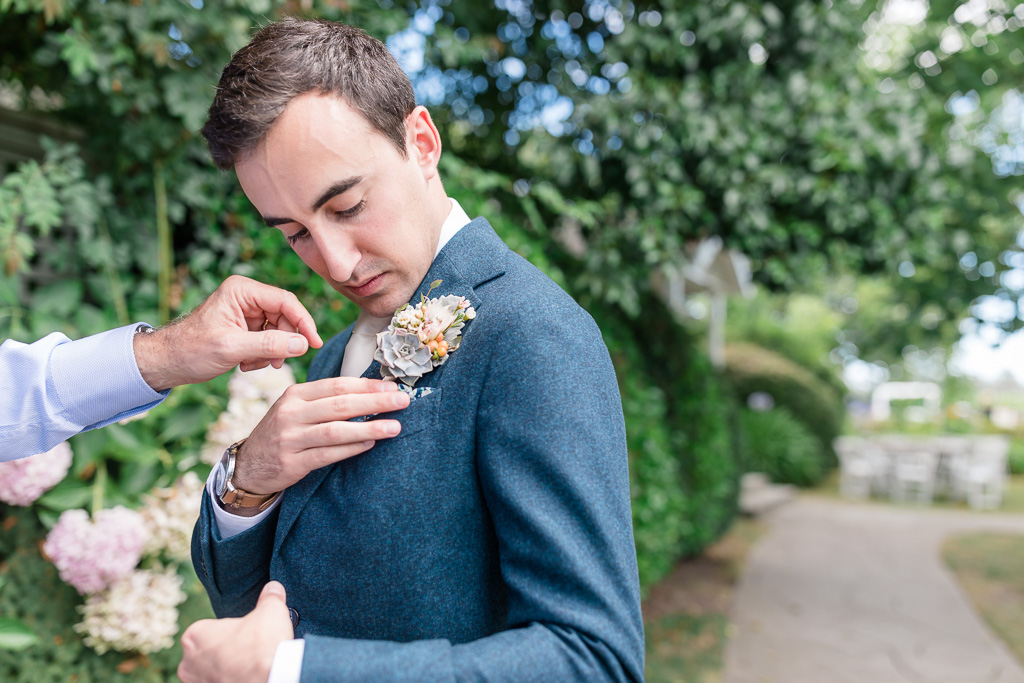 groom puts on the boutonniere