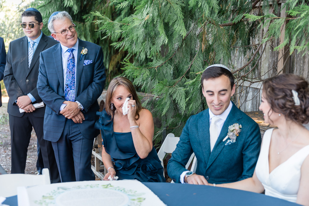 parents wiping happy tears at the ketubah signing