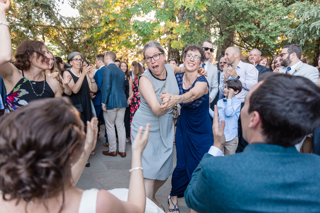 mother and rabbi entertain the newlyweds by some silly dance moves