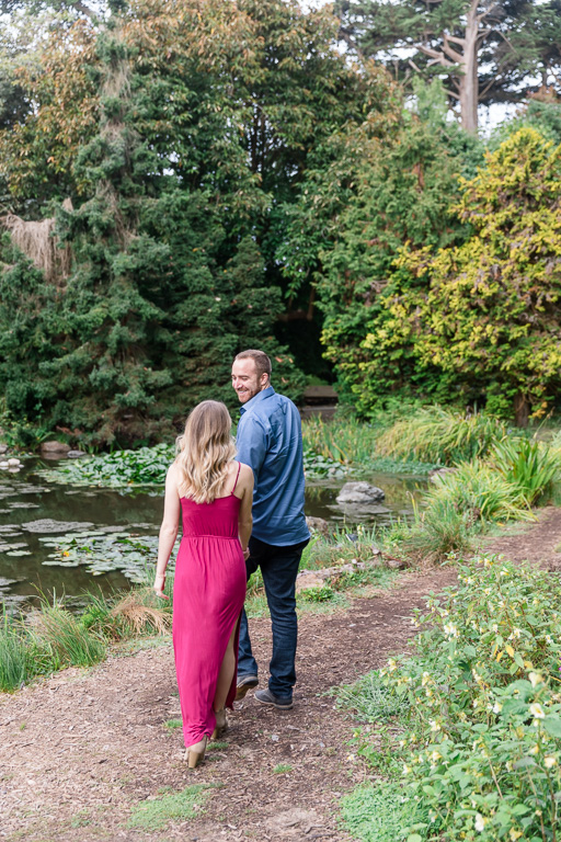 engagement photo walking along the path by the pond