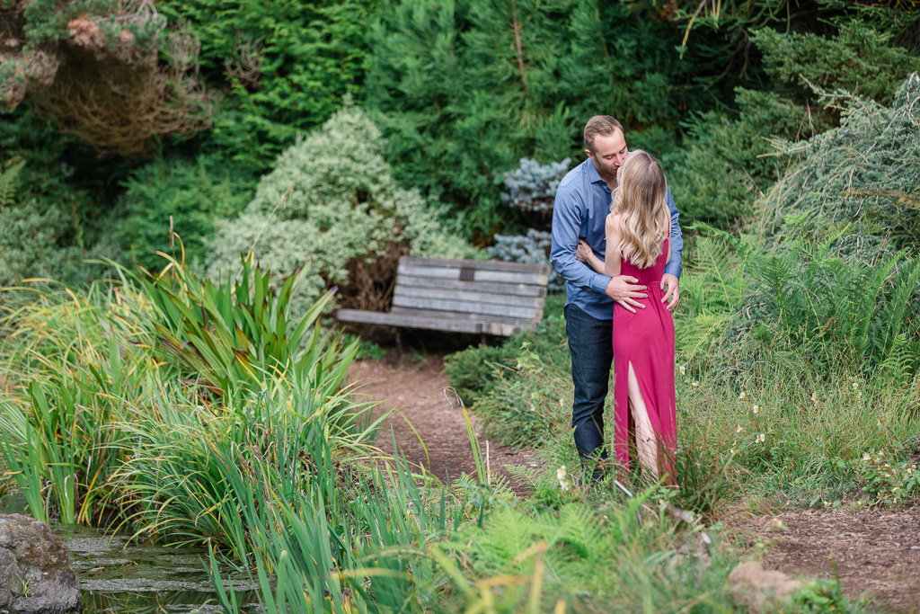 romantic kissing photo after their engagement at the SF Botanical Garden