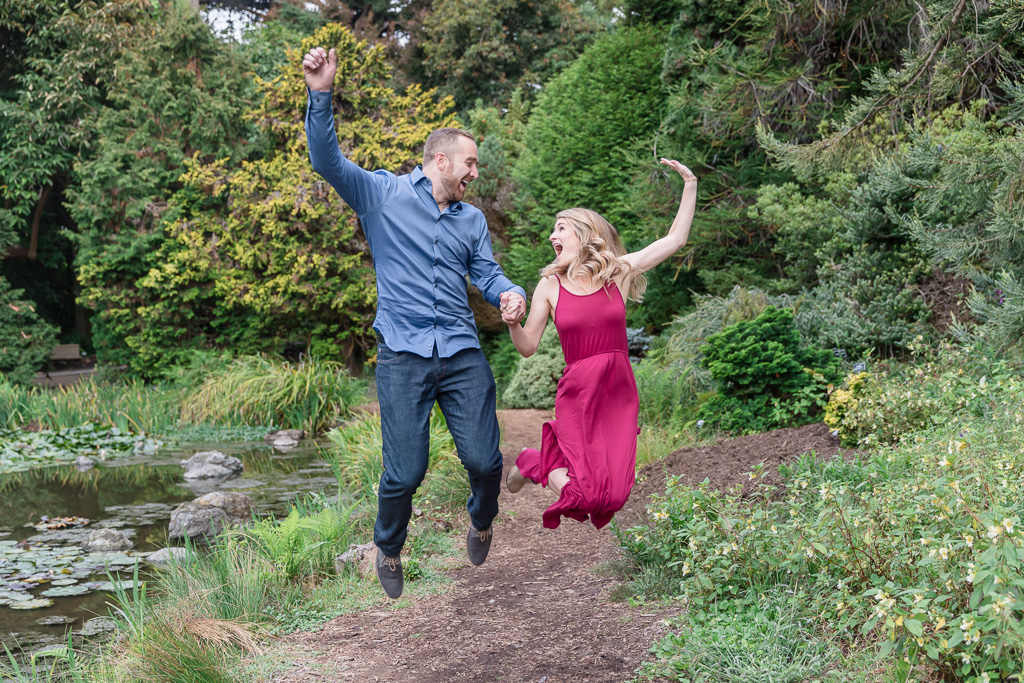 a cute jumping photo of the newly engaged couple