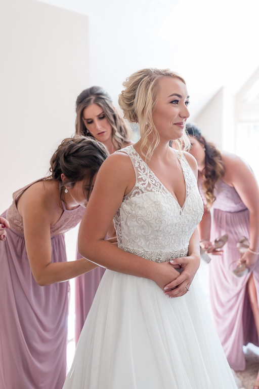 ladies helping bride to get into her dress