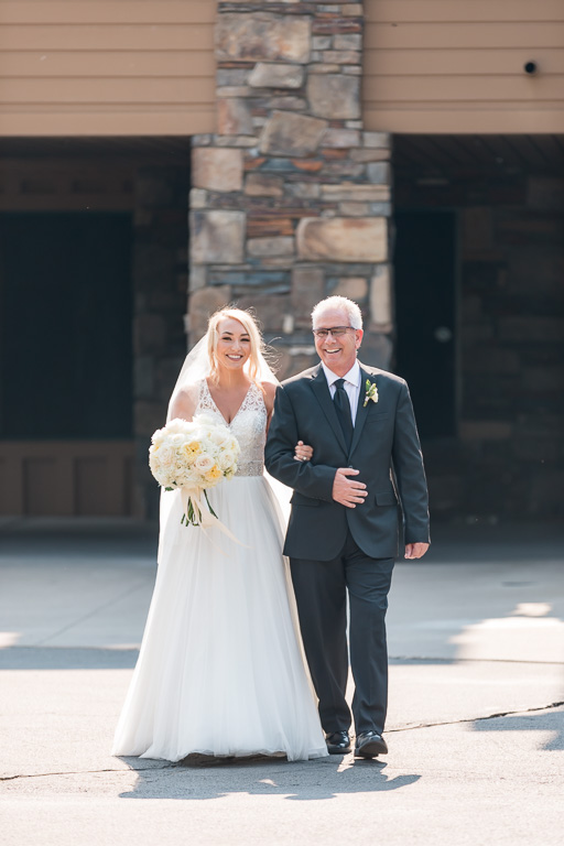 bride escorted by her father looking happy