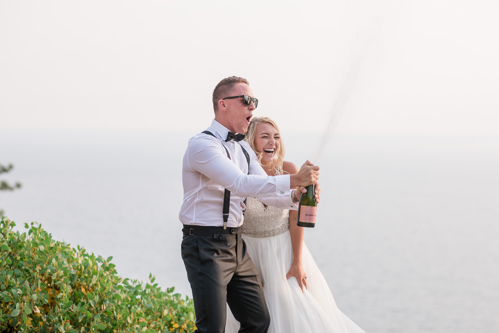 super fun wedding moment - bride and groom opening and uncorking a bottle of champagne