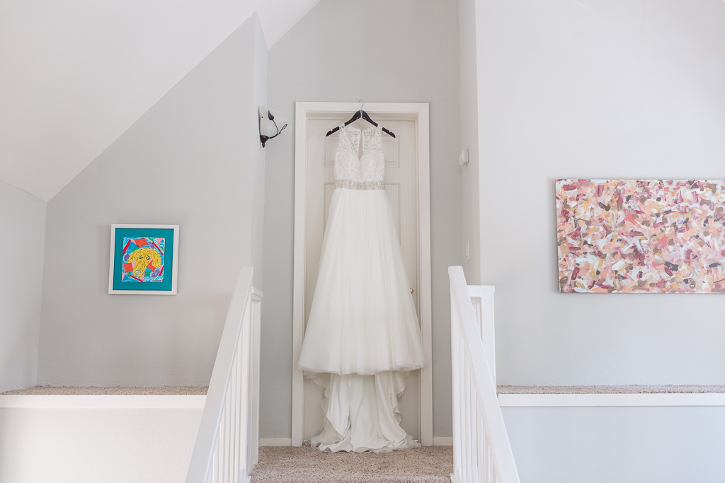 lace A-line wedding gown hanging on the door
