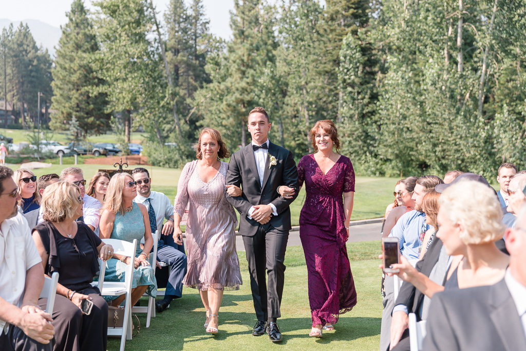 groom walking down the aisle escorted by mothers