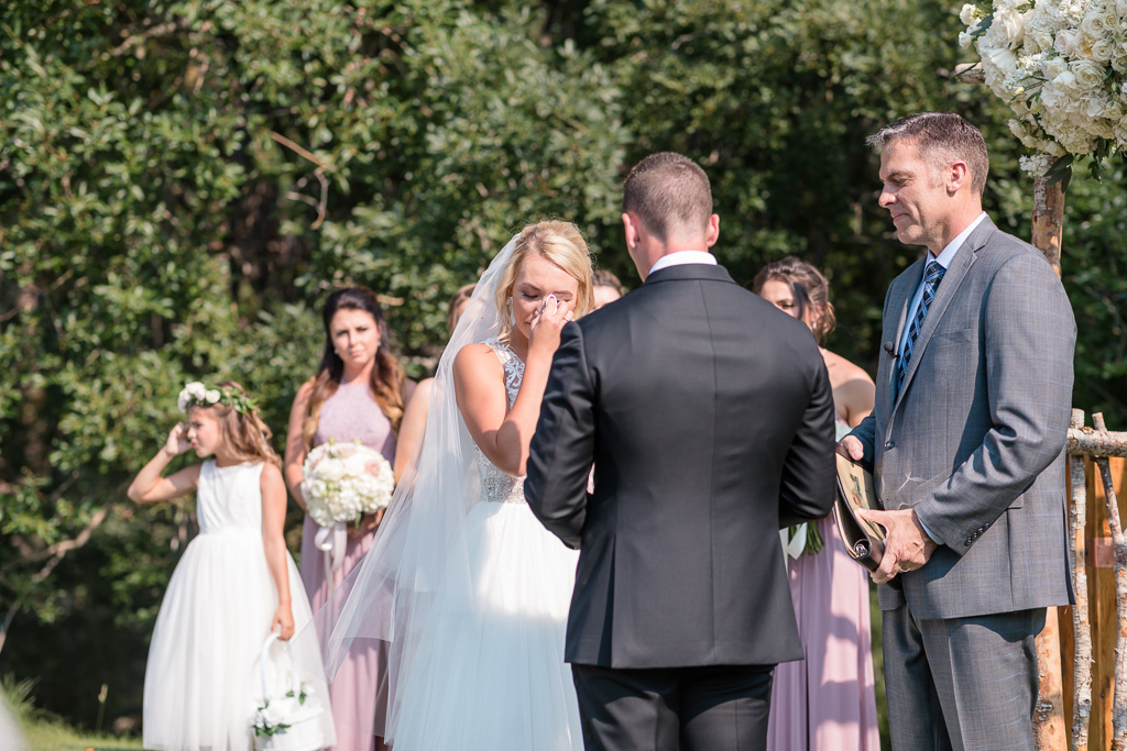 bride wiping her tears during groom's personal vows