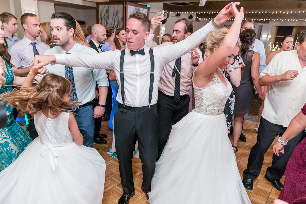 bride and groom dancing together with guests