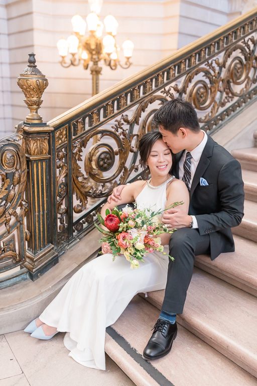 wedding photo sitting on the San Francisco City Hall grand staircase