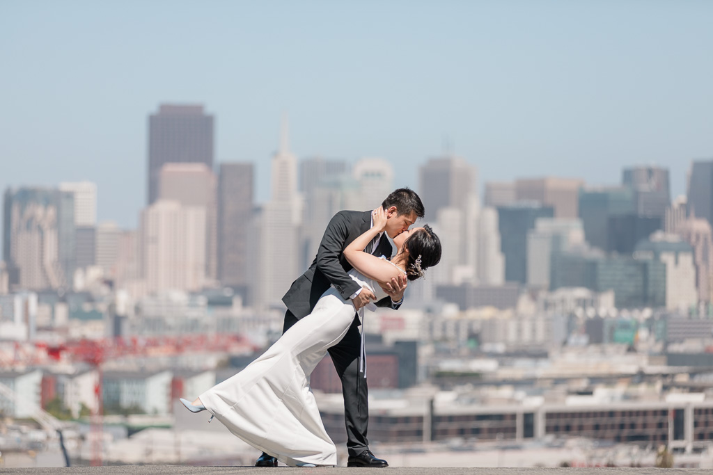 San Francisco wedding photo on top of the city with the skyline behind them