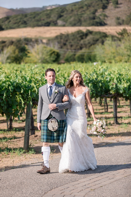 newlyweds walking along the vineyards to their reception