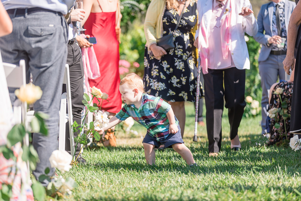 cute baby boy playing with the flowers on the ceremony aisle