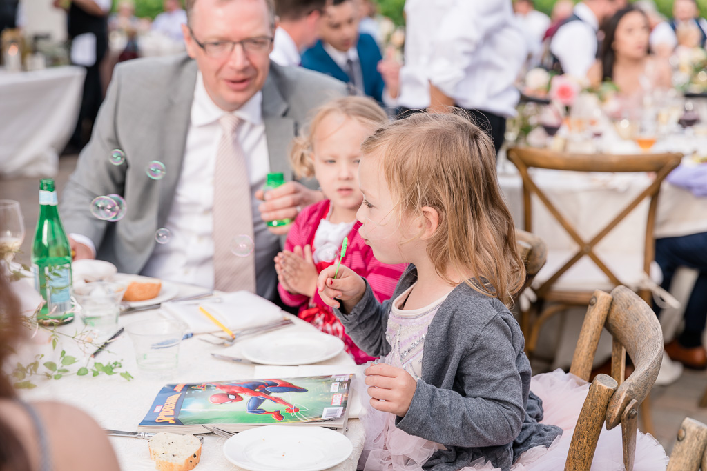 little wedding guests having fun blowing bubbles