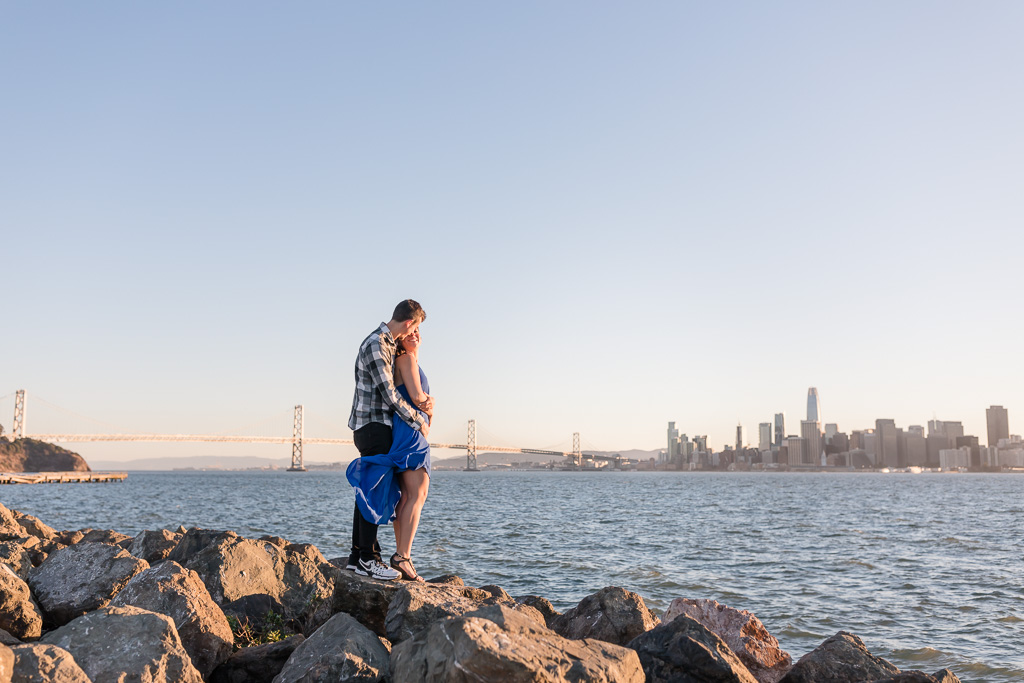 enjoying the San Francisco skyline view and the bridge during their engagement session